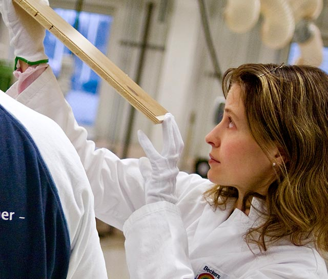 A woman scientist scrutinizes a paint sample with a colleague.