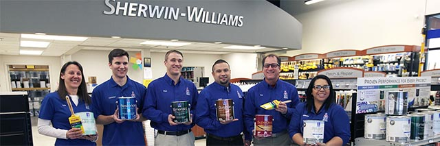 Six associates stand proudly together, each holding a different paint product.