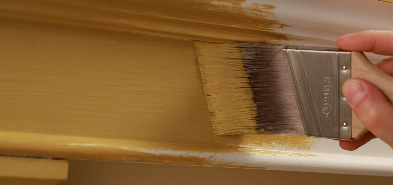 Close up of a paint brush painting a wall