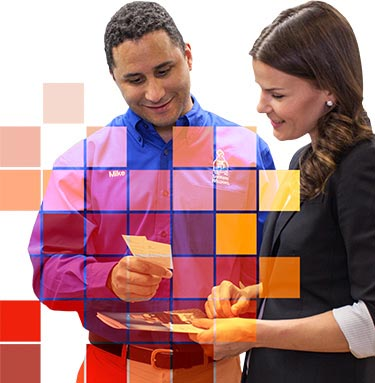 Salesman stands with a female professional helping her to pick out a paint color.